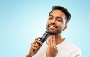 smiling-indian-man-shaving-beard-with-trimmer