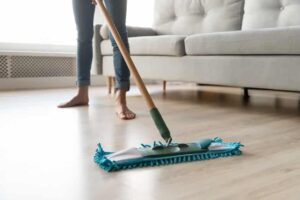 Woman housewife holding mop cleaning wooden floor at home